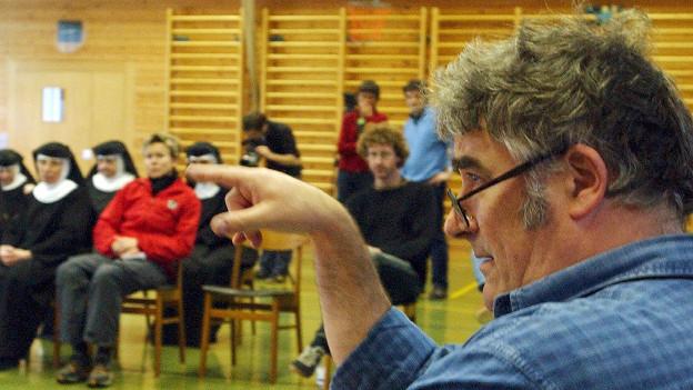 Fred Frith deutet mit dem Zeigefinger, im Hintergrund sitzen Menschen auf Stühlen, darunter auch Nonnen.