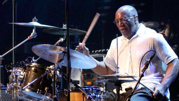 Billy Cobham sitzt an seinem Schlagzeug, er trägt ein weisses Hemd, die Augen geschlossen.
