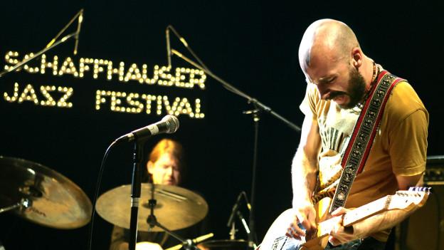 Gitarrist auf der Bühne, unscharf im Hintergrund ein Schlagzeuger.