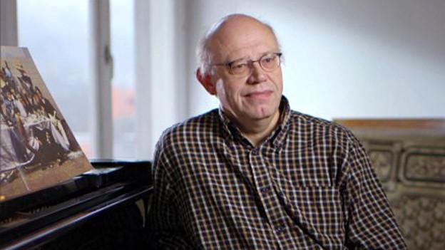 Porträt eines Mannes mit Halbglatze, Brille und kariertem Hemd.