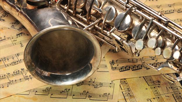 Ein Saxophon liegt auf Notenblättern.