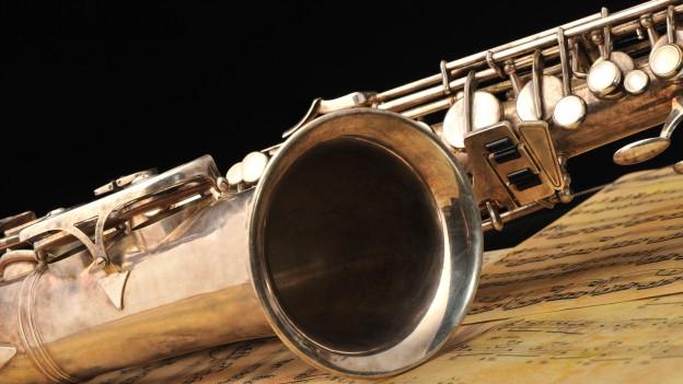 Saxofon liegt auf Notenblättern.
