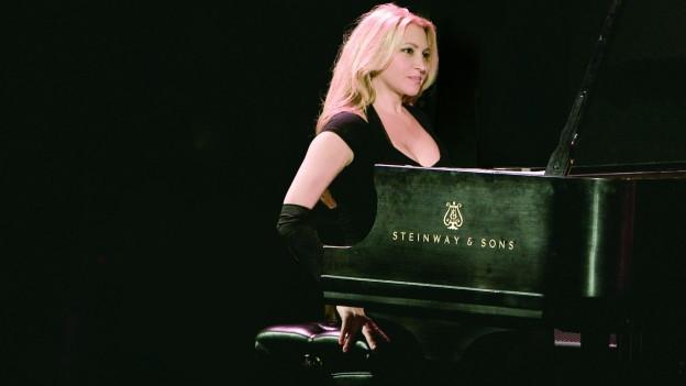 Eine Frau sitzt an einem schwarzen Flügel und spielt. Sie hat blonde, offene Haare und schwarze Kleidung.