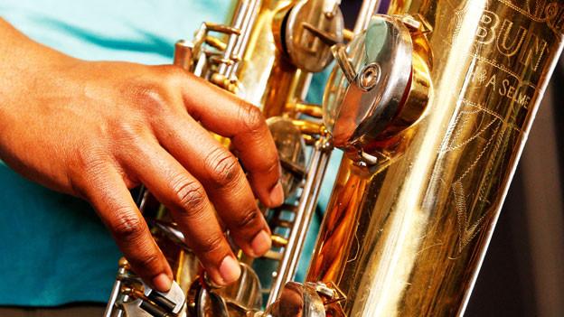 Eine schwarze Hand an einem goldenen Saxofon.