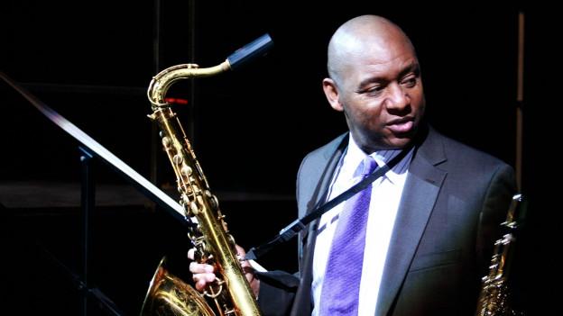 Nahaufnahme des Musikers während er Saxophon spielt, violett-blaues Licht.