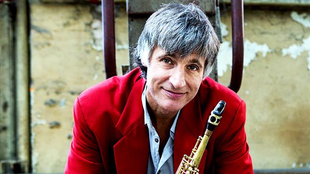 Ein Mann mit grauem, kurzem Haar hält ein Saxophon in der Han und schaut in die Kamera.