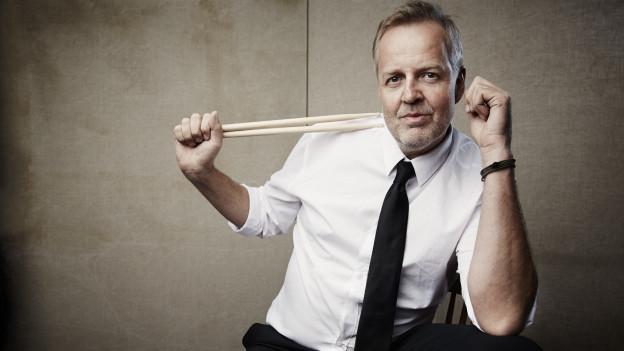 Ein elegant gekleideter Mann wirft sich mit Schlagzeugschlägern in Pose.