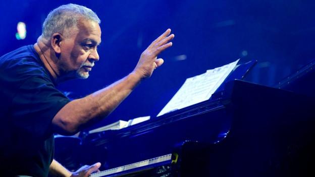 Ein Mann sitzt an einem Klavier. Die linke Hand hat er auf den Tasten, die rechte streckt er aus.