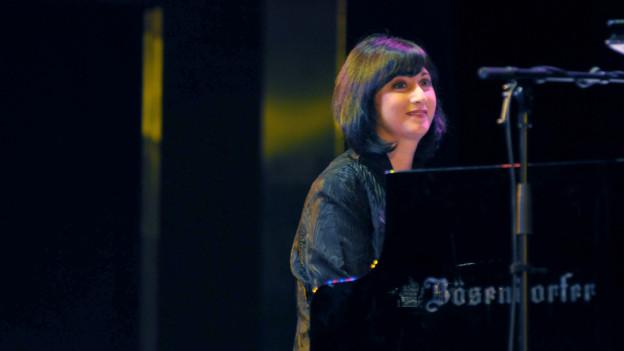 Eine Frau mit halblangem Haar sitzt an einem Konzertflügel.