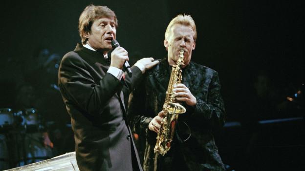 Ein Sänger im dunklen Anzug musiziert mit einem Saxofonisten.