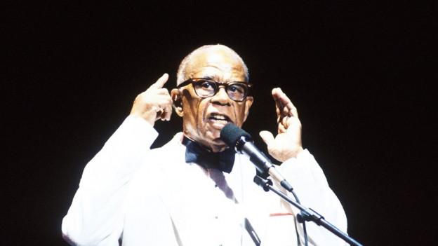 Ein dunkeläutiger Mann mit markanter Brille spricht in ein Mikrophon, die Hände erhoben.