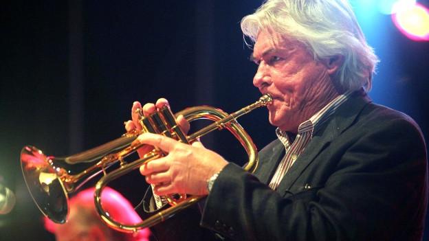 Ein Mann im Scheinwerferlicht: Er spielt Trompete, sein Haar ist halblang.