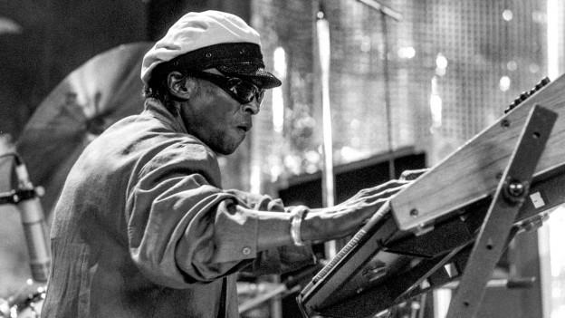 Schwarz-Weiss-Foto: Ein dunkelhäutiger Musiker mit Pilotenhut und Sonnenbrille.