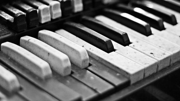 Schwarz-Weiss-Foto: Klaviertasten in Nahaufnahme.