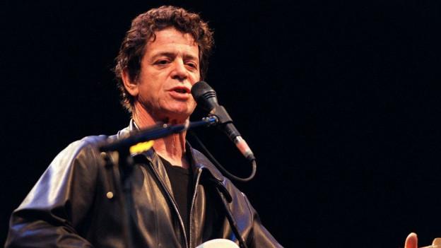 Lou Reed auf der Bühne mit Gitarre.