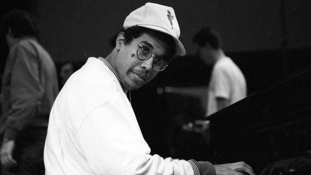 Schwarzweiss Foto von Danilo Perez, der am Piano sitzt.