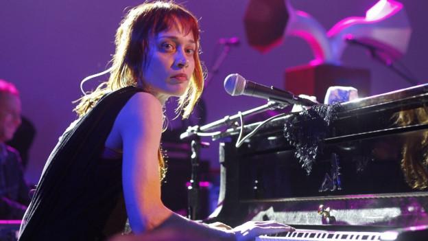 Die junge Frau sitzt am Klavier