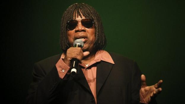 Ein Herr im Anzug, mit Sonnenbrille und ulkiger Frisur, singt in ein Mikrofon