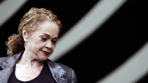 Eine geschminkte Frau in silbernem Blazer hat ihr langes, lockiges, rotblondes Haar am Hinterkopf zusammengebunden