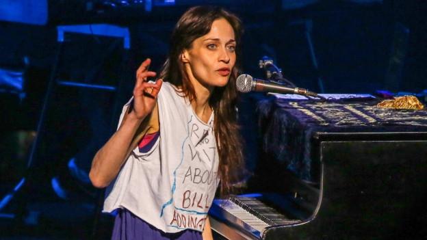 Frau mit langen braunen Haaren sitzt am Klavier
