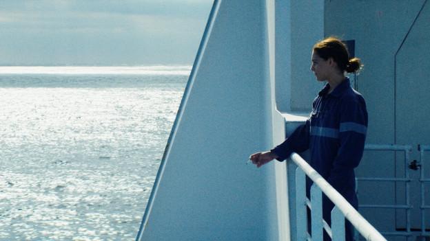 Eine Frau raucht einen Zigarette auf einem Schiff im Meer.