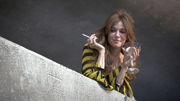 Frau mit Cocktailglas und Zigarette blickt von Balkon