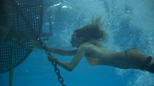 Eine junge Frau schwimmt unter Wasser eine Boje an