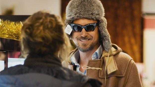 Mann mit Fellmütze und Sonnenbrille