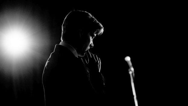 Mann mit Mikrofon auf Bühne in Gegenlicht