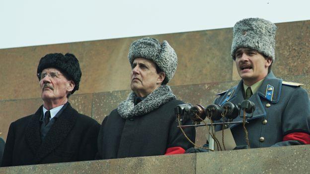 Drei Männer mit Pelzmützen auf Rednerpodest
