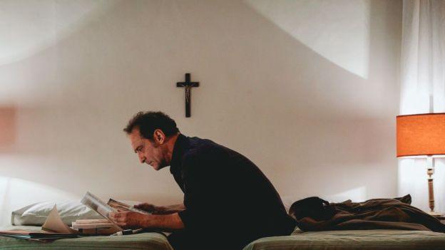 Mann auf Bett vor Kreuz an der Wand