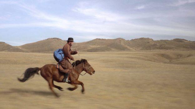 Mann reitet auf Pferd