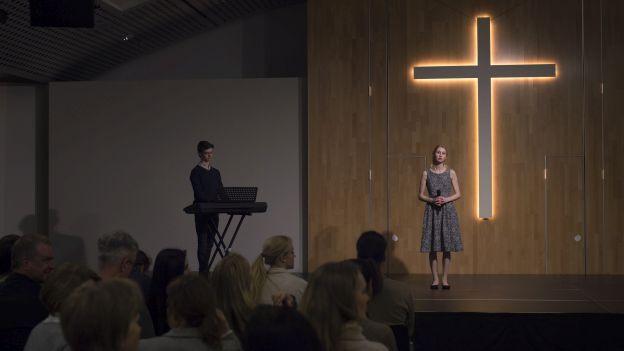 Frau in Kirche vor leuchtendem Kreuz