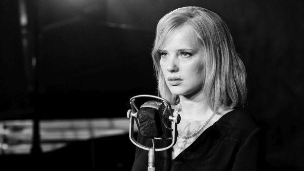 Frau auf Bühne vor Mikrofon