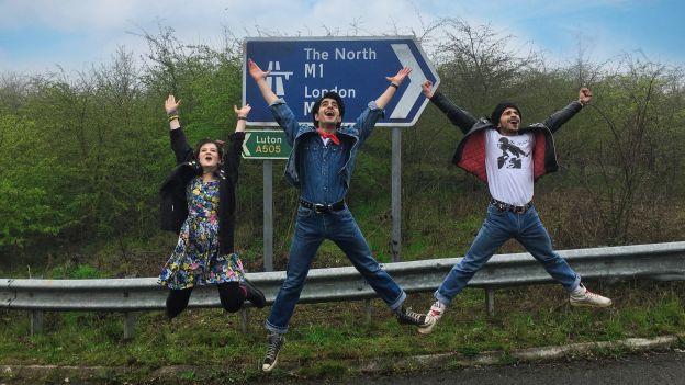 drei Jugendliche springen vor einem Strassenschild hoch