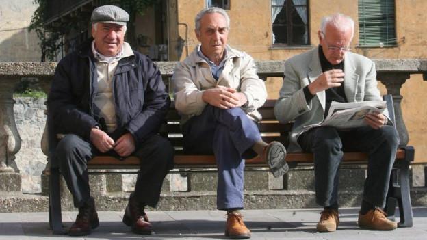 Ein paar italienische Männer sitzen auf einer Bank und geniessen das Leben.
