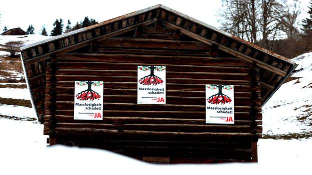 Eine Hütte im Schnee mit Abstimmungsplakaten der Befürworter des SVP-Initiative.