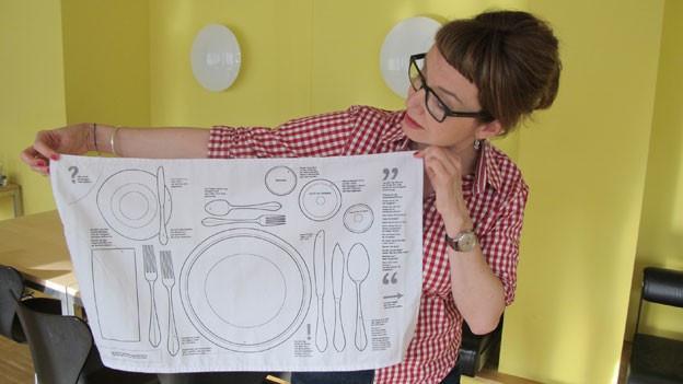 Eine Frau hält ein weisses Tuch hoch, auf dem aufgezeichnet ist, wie der Tisch korrekt gedeckt wird.