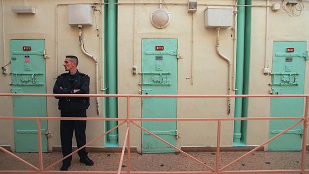 Ein Wärter steht vor Gefängnistüren