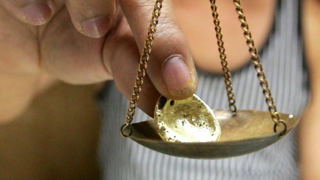 Eine Hand legt ein Goldstück in eine kleine Waagschale.