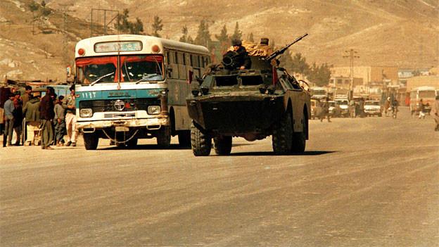 Eine Landstrasse mt Bus und gepanzertem Wagen mit Männern mit Maschinengewehr.