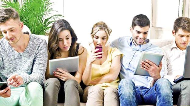 Menschen sitzen mit Handy, Tablet und Laptop auf Sofa.