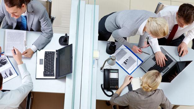 Auf dem Bild ist von oben die Ansicht auf zwei Bürotische, an denen Personen diskutieren und arbeiten.