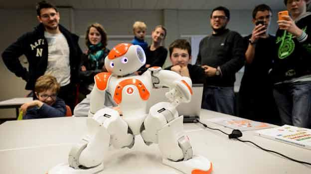 Mini-Robotter, vom Äusseren dem Menschen nachempfunden, tanzt auf einem Tisch.