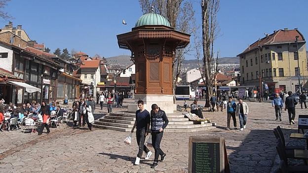 Die Fotografie zeigt den Sebilj-Brunnen auf dem alten Marktplatz von Sarajevo: Er ist aus dunklem Holz und gilt als Wahrzeichen.