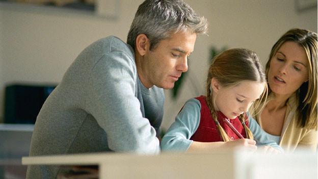 Eltern lernen zusammen mit ihrem Mädchen.