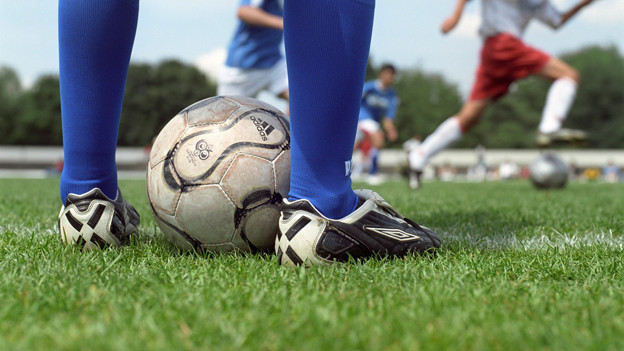 Füsse mit Fussballschuhen und ein Fussball am Spielfeldrand