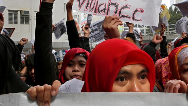 Demonstration von vielen Menschen, darunter Frauen mit roten Kopftüchern.
