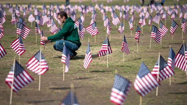 Ein Mann inmitten eines Feldes, auf dem kleine USA-Flaggen stecken. Der Mann richtet eine Flagge gerade.