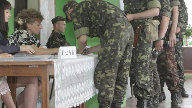 Ukrainische Soldaten geben ihre Stimme ab.